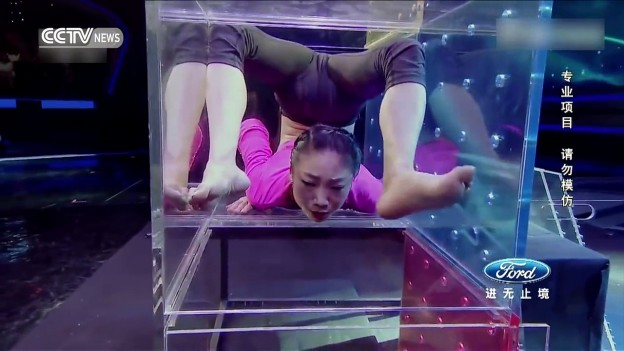 Extreme challenge: Acrobat contorts body to squeeze through boxes