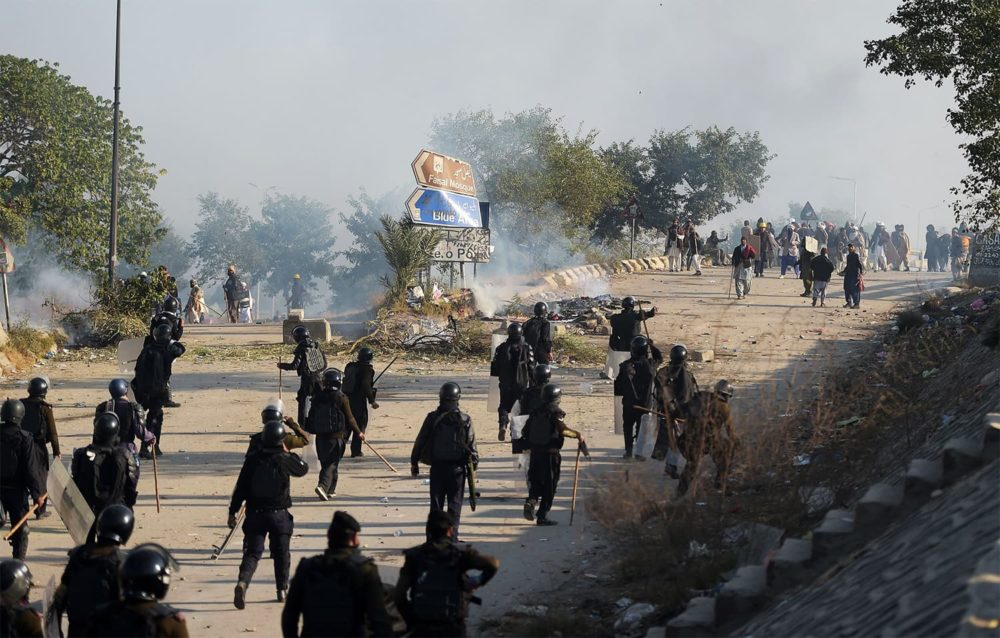 Pakistani riot policemen chase protesters from the Tehreek-i-Labaik Yah Rasool Allah Pakistan (TLYRAP) religious group during a clash in Islamabad on November 25, 2017. Pakistani forces fired rubber bullets and lobbed tear gas at protesters in Islamabad on November 25 as they moved to disperse an Islamist sit-in that has virtually paralysed the country's capital for weeks. The roughly 8,500 elite police and paramilitary troops in riot gear began clearing the 2,000 or so demonstrators soon after dawn, with nearby roads and markets closed. / AFP PHOTO / AAMIR QURESHI