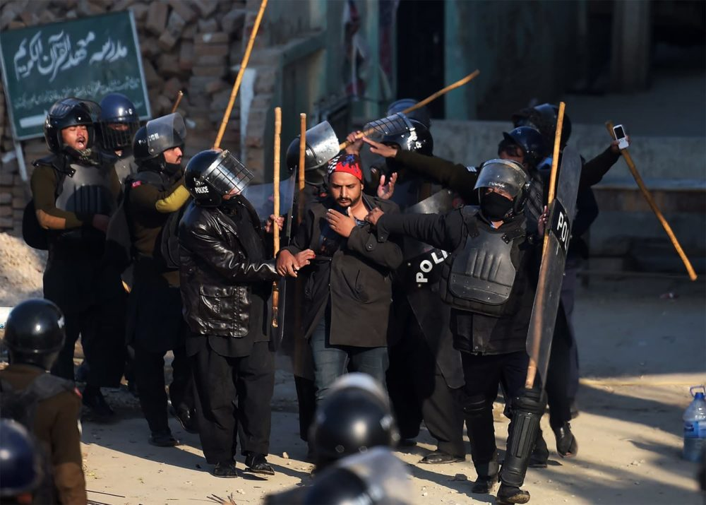 Pakistani riot policemen arrest an activist (C) from the Tehreek-i-Labaik Yah Rasool Allah Pakistan (TLYRAP) religious group during a clash in Islamabad on November 25, 2017. Pakistani forces fired rubber bullets and lobbed tear gas at protesters in Islamabad on November 25 as they moved to disperse an Islamist sit-in that has virtually paralysed the country's capital for weeks. The roughly 8,500 elite police and paramilitary troops in riot gear began clearing the 2,000 or so demonstrators soon after dawn, with nearby roads and markets closed. / AFP PHOTO / AAMIR QURESHI