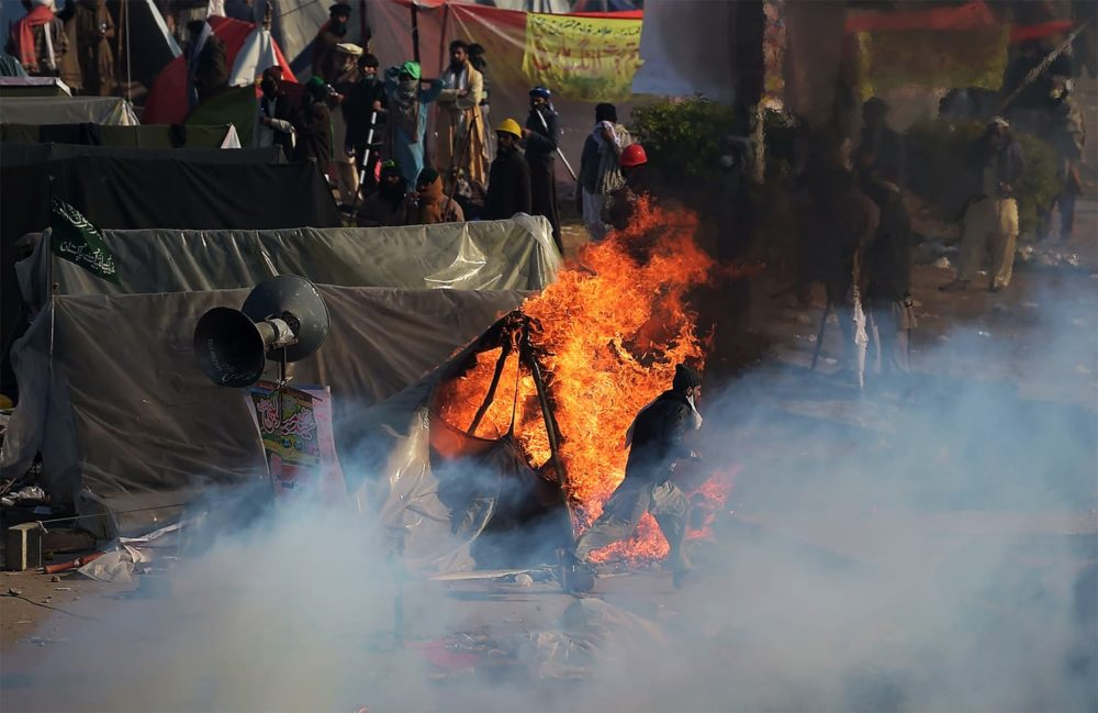 A Pakistani protester from the Tehreek-i-Labaik Yah Rasool Allah Pakistan (TLYRAP) religious group runs past a burning tent during a clash with police in Islamabad on November 25, 2017. Pakistani forces fired rubber bullets and lobbed tear gas at protesters in Islamabad on November 25 as they moved to disperse an Islamist sit-in that has virtually paralysed the country's capital for weeks. The roughly 8,500 elite police and paramilitary troops in riot gear began clearing the 2,000 or so demonstrators soon after dawn, with nearby roads and markets closed. / AFP PHOTO / AAMIR QURESHI