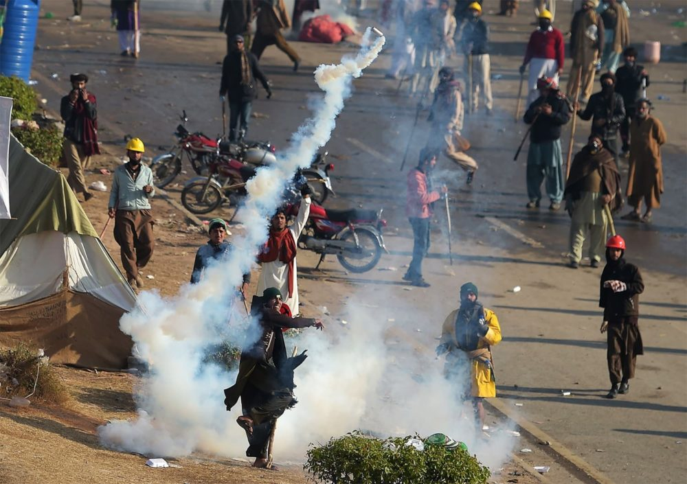 A Pakistani protester of the Tehreek-i-Labaik Yah Rasool Allah Pakistan (TLYRAP) religious group throws a tear gas shell back towards police during a clash in Islamabad on November 25, 2017. Pakistani forces fired rubber bullets and lobbed tear gas at protesters in Islamabad on November 25 as they moved to disperse an Islamist sit-in that has virtually paralysed the country's capital for weeks. The roughly 8,500 elite police and paramilitary troops in riot gear began clearing the 2,000 or so demonstrators soon after dawn, with nearby roads and markets closed. / AFP PHOTO / AAMIR QURESHI