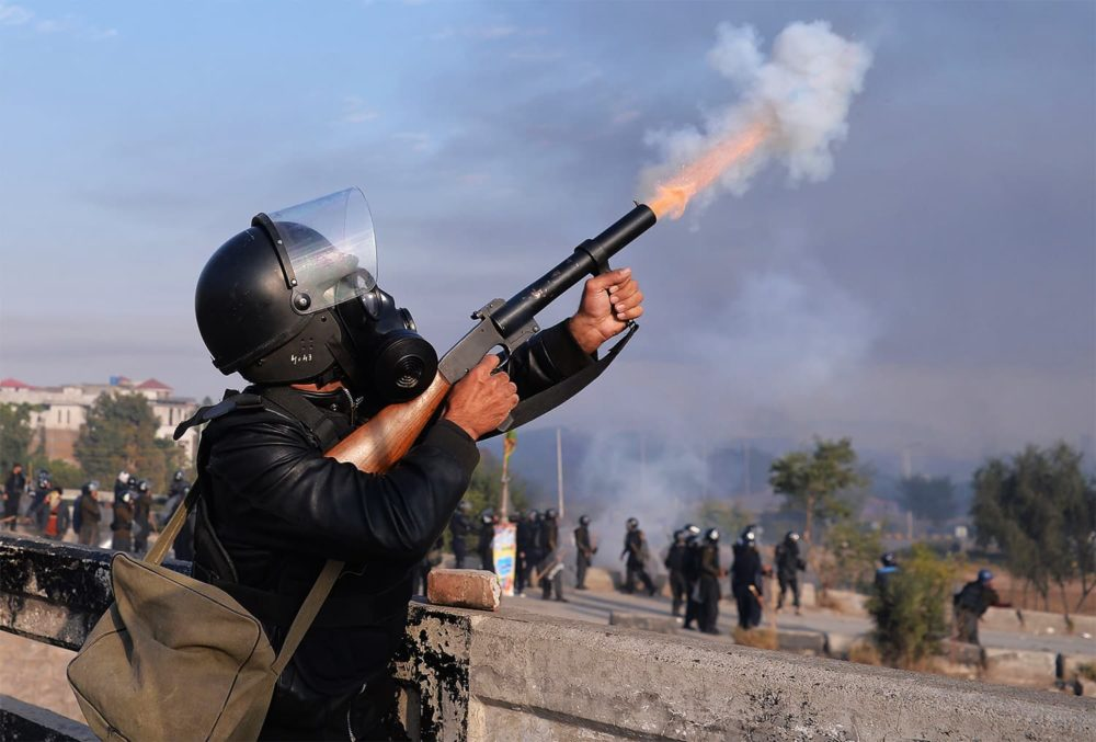 A Pakistani policeman fires at protesters from the Tehreek-i-Labaik Yah Rasool Allah Pakistan (TLYRAP) religious group gather during clashes in Islamabad on November 25, 2017. Pakistani forces fired rubber bullets and lobbed tear gas at protesters in Islamabad on November 25 as they moved to disperse an Islamist sit-in that has virtually paralysed the country's capital for weeks. The roughly 8,500 elite police and paramilitary troops in riot gear began clearing the 2,000 or so demonstrators soon after dawn, with nearby roads and markets closed. / AFP PHOTO / AAMIR QURESHI