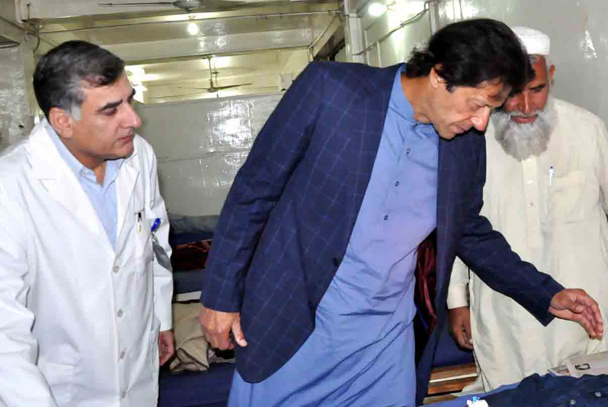 PESHAWAR: Chairman PTI Imran Khan enquiring about the health of injured persons of earthquake during his visit to Lady Reading Hospital. INP PHOTO