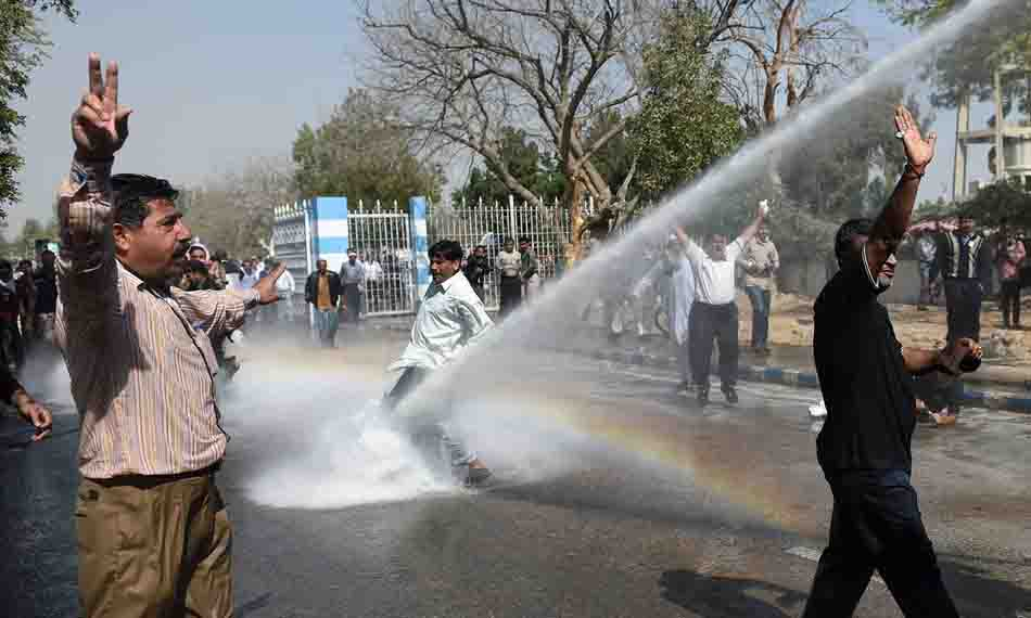 Pakistani employees of Pakistan International Airlines (PIA) shout slogans as police use a water cannon on them during a protest near Karachi International Airport in Karachi on February 2, 2016. Two demonstrators were shot dead and several more were wounded at Karachi's international airport when clashes broke out between security forces and staff from the national airline protesting privatisation plans, officials said. AFP PHOTO / RIZWAN TABASSUM