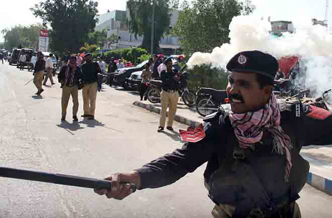 Px02-021 KARACHI: Feb02 - Policemen use batons and tear gas to disperse the employees of Pakistan International Airlines (PIA) who were stopped from going towards Jinnah International Airport during their protest rally against the privatization of the airlines. ONLINE PHOTO by Sabir Mazhar
