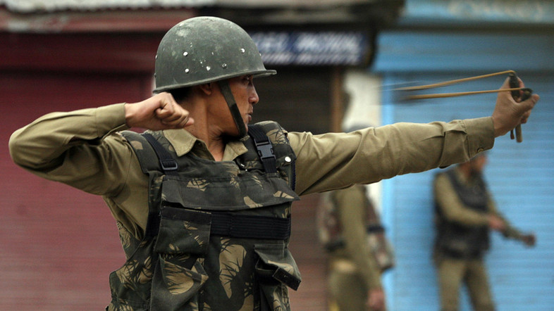 An Indian policeman uses a sling shot to throw stones at Kashmiri protesters during an anti-election protest in Srinagar May 8, 2009. At least 30 people were injured when Indian police in Kashmir's main city fired teargas shells on Friday to disperse thousands of Muslims protesting against India's general election in the disputed Himalayan region, police and witnesses said. They said more than 6,000 protestors led by the region's senior separatist leader and chief cleric, Mirwaiz Umar Farooq, marched through the streets in downtown Srinagar, Kashmir's summer capital.  REUTERS/Fayaz Kabli    (INDIAN-ADMINISTERED KASHMIR CONFLICT POLITICS ELECTIONS IMAGES OF THE DAY) - RTXEXHZ