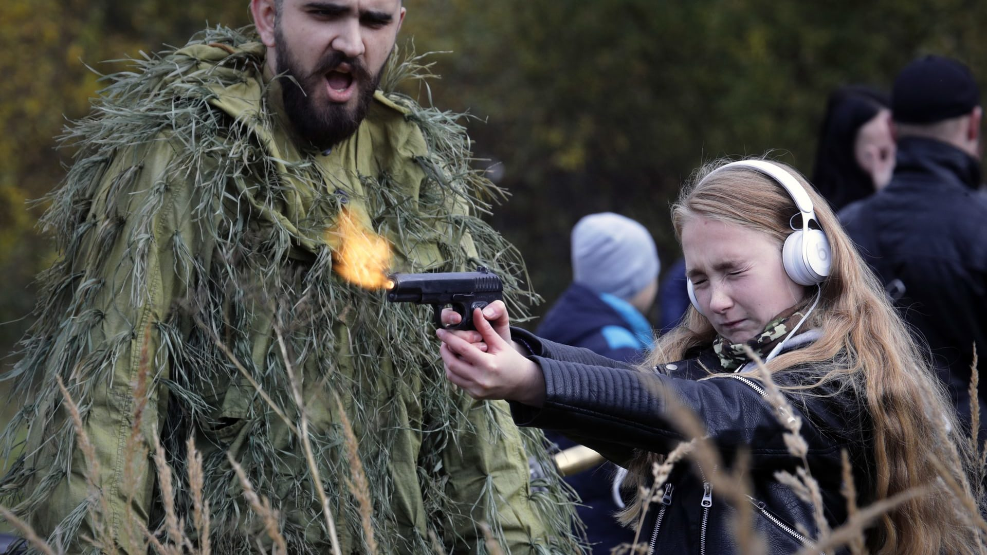 St Petersburg, Russia A girl shoots a gun filled with blanks at a weapons exhibition during a military show Photograph: Dmitri Lovetsky/AP