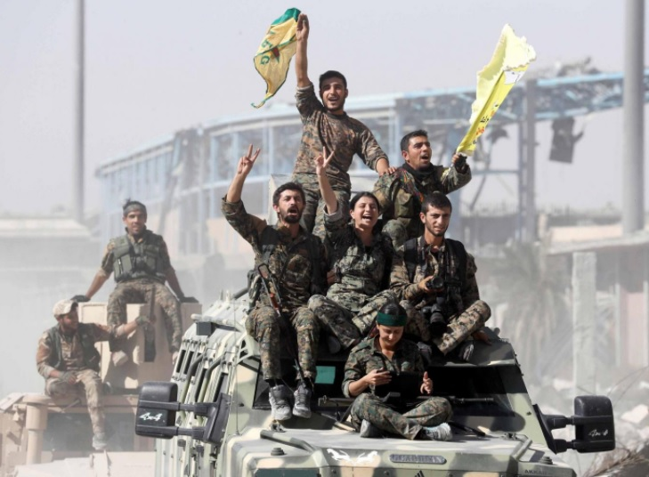Syrian Democratic Forces (SDF) fighters - Syrian Democratic Forces (SDF) fighters ride atop of military vehicles as they celebrate victory in Raqqa