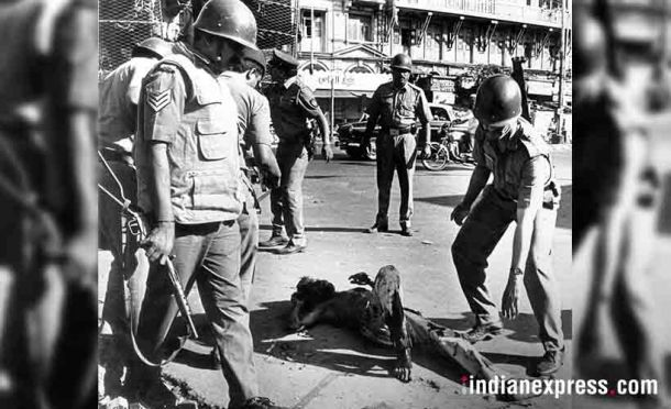 A stabbed person laying on street at Bhindi Bazar during 1992-93 Bombay riots. Police personnel trying to help him. Source: Express archive photo
