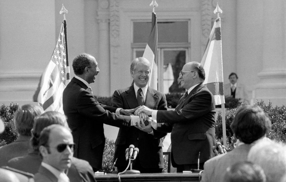 Egyptian President Anwar Sadat, U.S. President Jimmy Carter, and Israeli Prime Minister Menachem Begin clasp hands on the north lawn of the White House in Washington, D.C., on March 26, 1979, as they completed the signing of the peace treaty between Egypt and Israel.