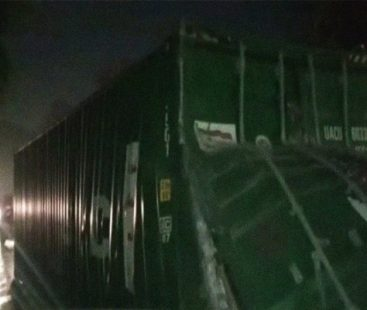 Passersby fetch dispersed cosmetics as truck container loaded with cosmetics topples