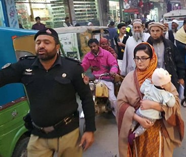 In the line of duty:Peshawar official Sara Tawab Umar performs duty while carrying infant daughter